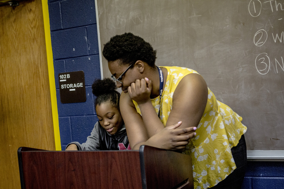 Aleigha Hall, a librarian at Cornelia Crenshaw, talks with Jernya, 11, during an event for Mother's Day.