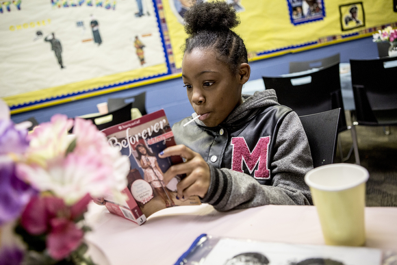 Jernya, 11, reads from one of her books while hanging out at the Cornelia Crenshaw Library.
