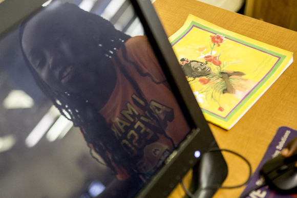 Rayjenae, 7, is reflected in the computer she's using at the Cornelia Crenshaw Library.