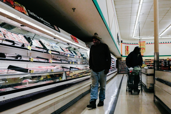 Two patrons of the Orange Mound Kroger browse the meat aisle. (Brandon Dahlberg)