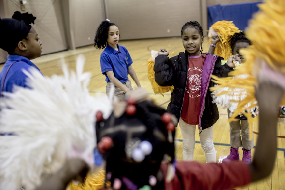 Girls in the Dave Wells Community Center's cheer squad play with their pompoms before practice.
