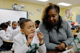 Johnathan Bush, 7, examines a rock during a science lession as Dr. Collins looks on. (Brandon Dahlberg)