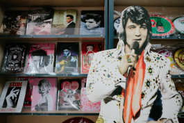 A cardboard Elvis display in front of various signs at Boulevard Souvenirs. (Brandon Dahlberg)