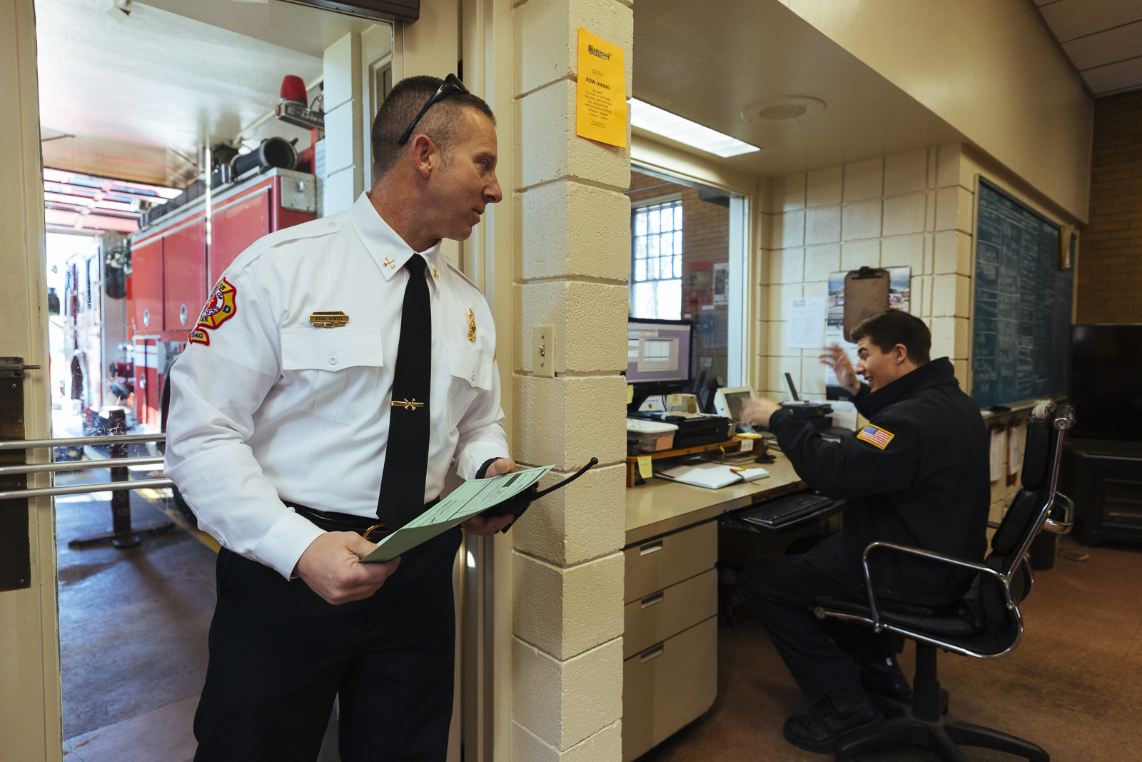 Twenty-year veteran Shane Howell (left) stops by with paperwork as Private Michael Pence (right) works the Station 18 desk where crew members field emergency calls and help citizen who walk in with an emergency. (Ziggy Mack)