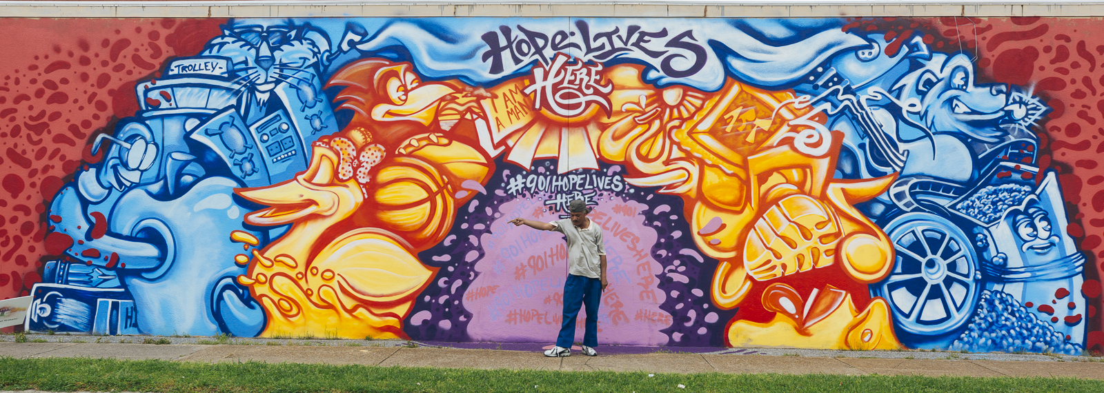 "Local musician ""Morris"" poses in front of a Madison Heights mural by artist Toonkey Berry. (Ziggy Mack) <span class=&apos;image-credits&apos;></span>"