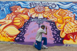 "Local musician ""Morris"" poses in front of a mural by artist Toonkey Berry. (Ziggy Mack)"