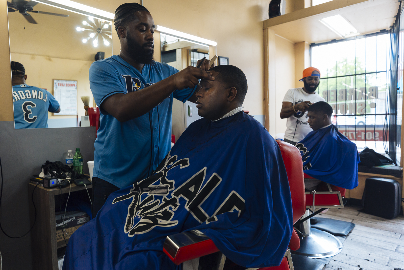L to R: Upscale Kutz Barber Shop barbers Karlos Burt cuts the hair of Riko while Dennis Ross cuts the hair of Bernard in the Madison Heights District. (Ziggy Mack)