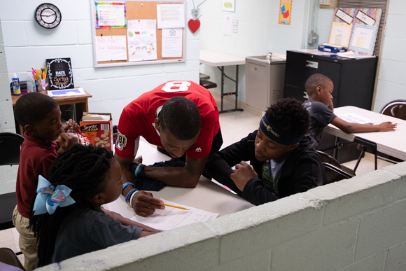 Timothy Williams, who works mostly with high school students, assists some of the kids with their homework at Oasis of Hope. (Brandon Dahlberg)