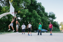 Young men play basketball in Booker T. Washington park.