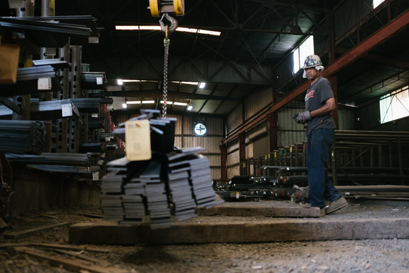 A worker lifts a stack of material with an overhead crane at Southern Steel. (Brandon Dahlberg)