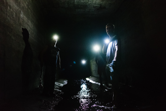 Four urban explorers make their way up the Gayoso Bayou, navigating by flashlight. (Brandon Dahlberg)