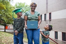 Marquetta Wilson poses with her children and her high school diploma. Wilson earned her diploma from the Goodwill Excel Center in June 2020 at 30 years old. Excel's adult learning program is free to participants. (Ziggy Mack)