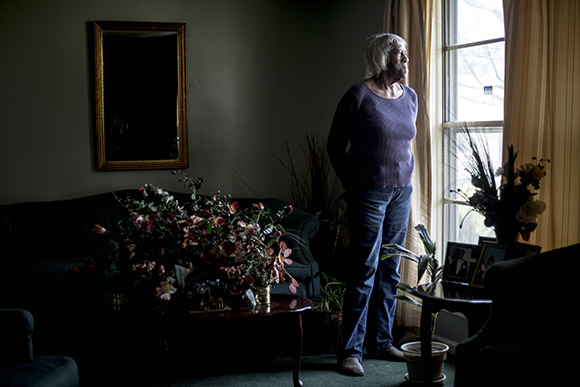 Mary Hill, 82, stands for a portrait at her home in Smokey City. She used to work at the Sears-Roebuck building as a waitress and has watched the neighborhood change over the years.