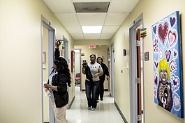Christine Jones and her mother Irma (behind) walk down the hall toward an exam room while being seen at the Guthrie Primary Care Clinic in Smokey City, North Memphis. (Andrea Morales, 2017).
