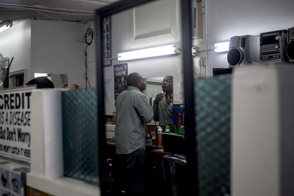 Derek Stubbs, a barber at the Handy Spot, trims his beard before sitting for a haircut.