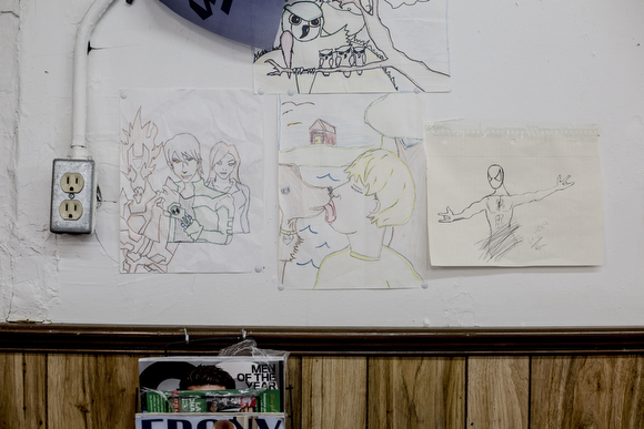 Eric Steward has drawings by his son hanging on many of the walls of the Handy Spot, the barber shop that has been in his family for decades.