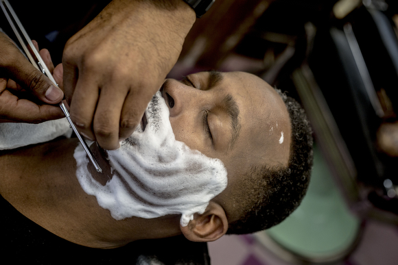 "Michael Harris gets a shave from Eric Steward, owner of the Handy Spot on Vollintine Avenue in Klondike. ""You can pretty much fall asleep in the chair if you trust your barber,"" Steward said."