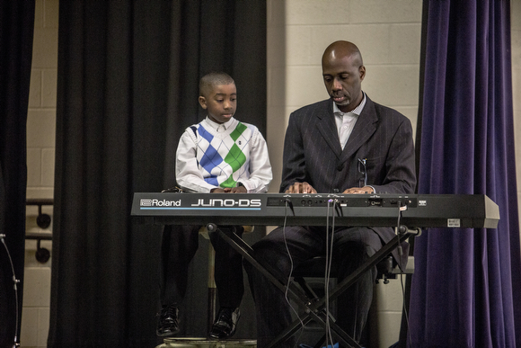 William Griffin and his son Joseph, 7, play the keyboard during Sunday service at Hope City Church in Caldwell-Guthrie's cafeteria in Smokey City.
