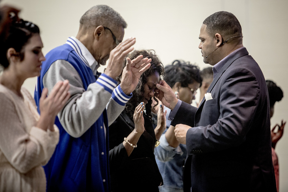Pastor Colley Cooper blesses people on the forehead with some holy water during Sunday service at Hope City Church in Caldwell-Guthrie's cafeteria in Smokey City.