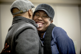 Angela Adair hugs her husband Robert during Sunday service at Hope City Church in Caldwell-Guthrie's cafeteria in Smokey City.