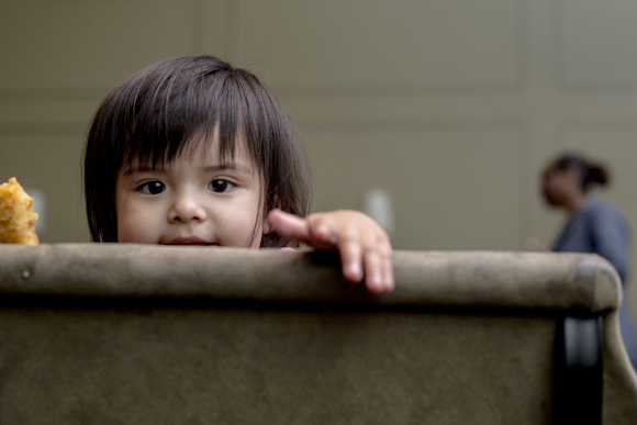 Azaylia Elias, 1, peeks out over a chair at the Operation Smart Child program at the Neighborhood Christian Center in Smokey City.