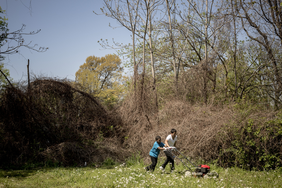 Jason Ayers helps Yalon Wallce, 10, mow through the high grass and weeds in an empty lot on Randle Street in Klondike. Folks from the community organization Crowning Our Youth, Inc. an anti-violence and youth oriented group, worked to clean up vacant