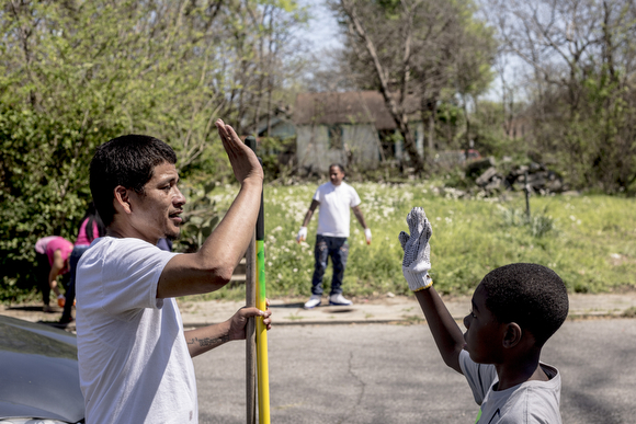 Jason Ayers high fives one of the kids that came out to help clean up empty lots along Randle Street in Klondike. Folks from the community organization Crowning Our Youth, Inc. an anti-violence and youth oriented group, worked to clean up vacant lots