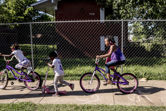 Girls ride their bikes down Tate Avenue past a boarded up apartment complex.
