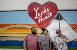 Jeremy Stein, general manager for Lucky Heart Cosmetics stands with Bennie Franklin, an employee of 33 years, and Olivet Montgomery, an employee of 52 years, by the mural outside the company's new storefront on Dr. Martin Luther King Boulevard.