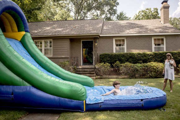 Epic Bouncing clients test out the slide and pool after it was set up in their yard for a party.