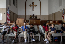 Children in the third grade group sit in the chapel during a reading lesson at the Emmanuel Center.