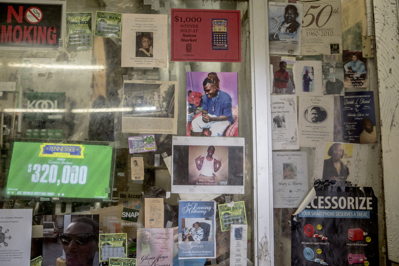 Photos of community members hang on the glass at Salem's Market on Mississippi Avenue. The store has been open for decades in the neighborhood and has seen a significant slowing of business since Foote Homes closed and demolition started.