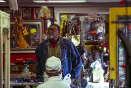A customer looks around the store as he speaks with the owner of the Summer Outlet thrift store. (Natalie Eddings)