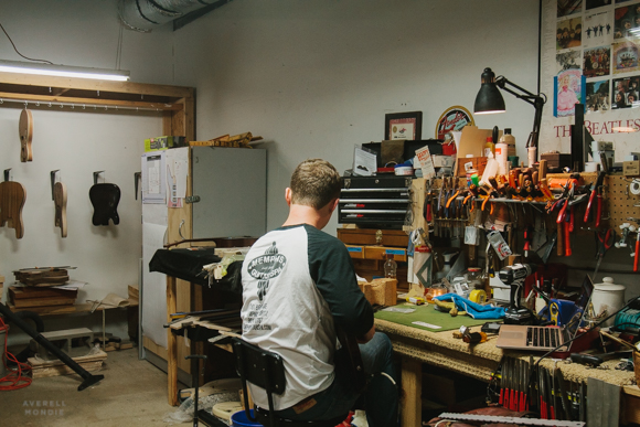 Hans Hilboldt at his workbench working on the strings of a guitar