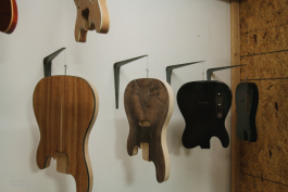 Guitar bodies hang in the workshop waiting to be connected with necks.