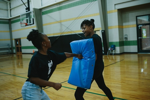 Girls Inc. counselor Brittney Wiliams instructs the girls in self-defense exercises.