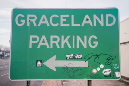 A graffitied sign for Graceland Parking on Elvis Presley Boulevard. (Brandon Dahlberg)