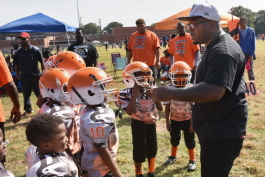 Orange Mound Raiders founder and coach Antonio Huntsman gives a pep talk to young football players in his sports and mentoring non-profit during a Saturday morning game.