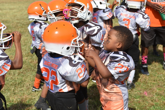 Teammates help each other adjust helmets as the Orange Mound Raiders prepare for a game.