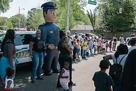 Sergeant Biggs, a Memphis Police Department mascot, greets members of the community outside Cathedral of Faith during the Klondike-Smokey City foster care awareness parade. (Brandon Dahlberg)