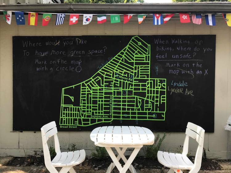 A once-drab building, 751 National Street now has tables and chairs, interactive maps of the neighborhood, and flags denoting the many nationalities in The Heights. (Cole Bradley)
