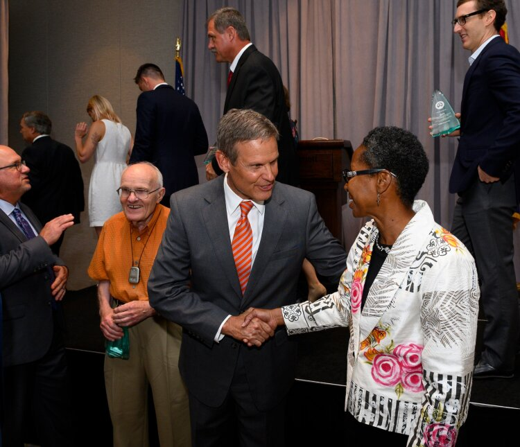 Dana Merriweather, founder and vice president of the Mitchell Heights Neighborhood Association, shakes hands with Governor Bill Lee at a luncheon for winners of the 2019 Tennessee Governor's Award for Environmental Stewardship. (TN Green Gov)