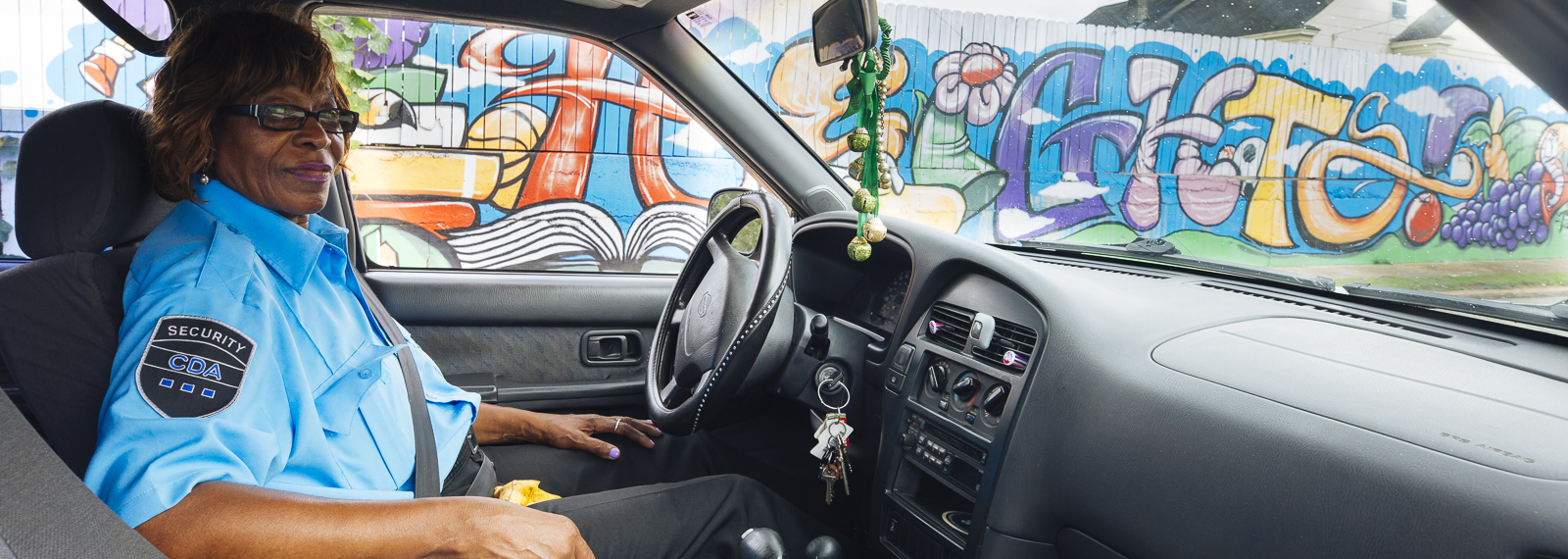 Heights resident Ethel McBride drives to work in front of a community mural near Treadwell Elementary and Middle School grounds.  <span class='image-credits'>Ziggy Mack</span>