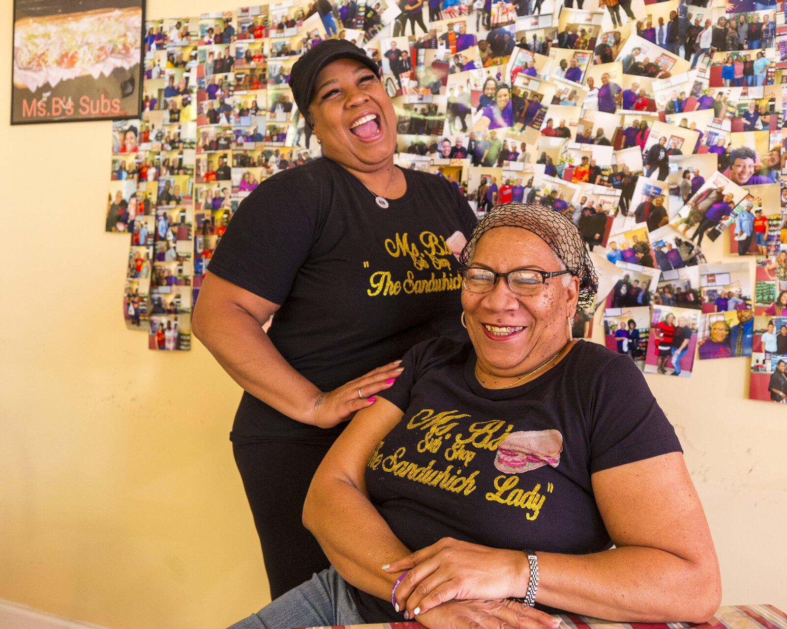 Stacy Bizzard (L) and her mother, Bonnie Harris, are co-owners of Ms. B's Sub Shop. They pose here in front of a wall of photos of satisfied customers. (Ziggy Mack)