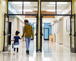 Amon Dillan walks holds hands with a Harwood Center student was they walk down the hall of their Cordova location inside Hope Church. January 27, 2020. (ZIggy Mack)