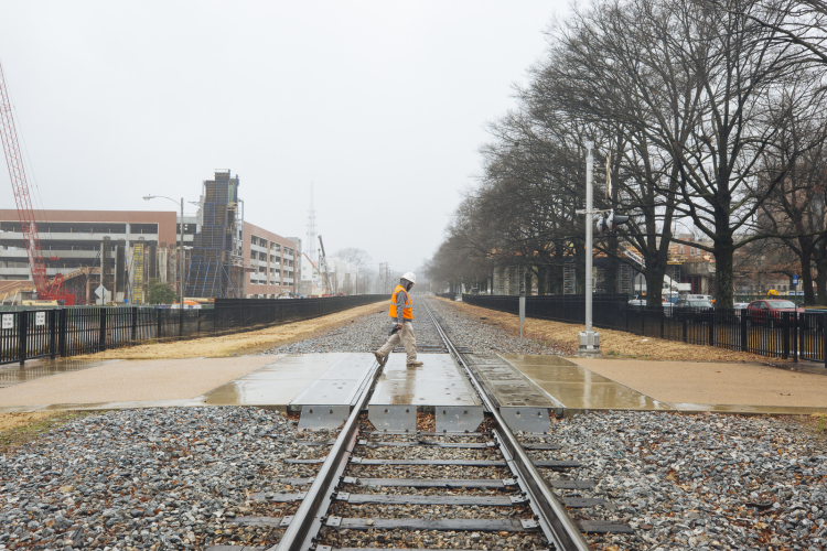 A construction worker crosses the train tracks at Southern Avenue. In the background, the University of Memphis' pedestrian bridge is under construction. (Ziggy Mack)