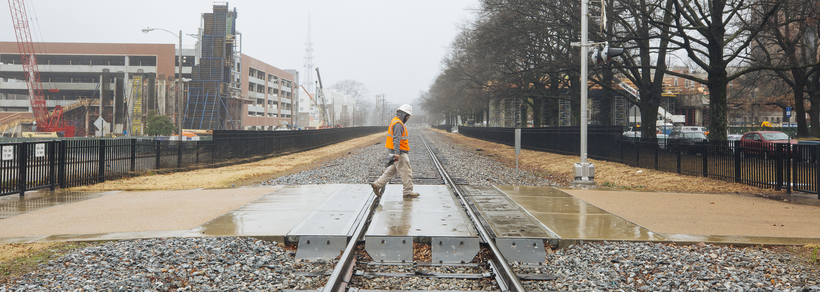 A construction worker crosses the railroad tracks at the University of Memphis with the pending pedestrian under construction in the far background. (Ziggy Mack) <span class='image-credits'></span>