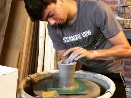 Belltower co-owner Micah Dempsey works on a pottery mug.