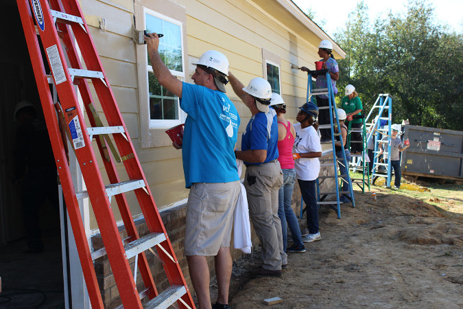 Volunteers and the actual home owners work on painting the new home in Oakhaven in S. Memphis.