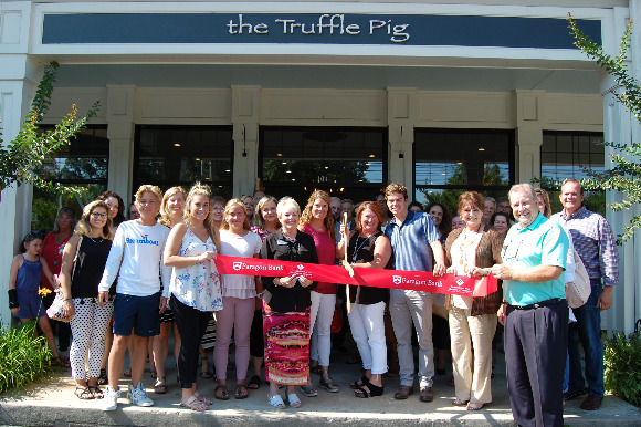The Truffle Pig owners Tara  Gorman and Tricia Atkins (holding scissors) celebrate store opening.